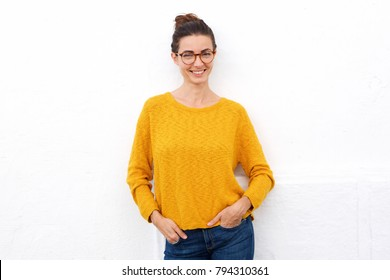 Portrait of attractive young woman smiling with glasses against white wall