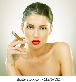 portrait of attractive young woman smoking cigar, studio background - vintage picture style