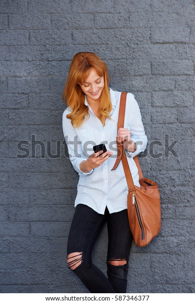 Portrait of attractive young woman standing with mobile phone