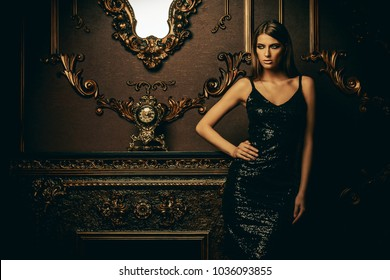 Portrait of an attractive young woman in tight black dress in a luxury apartment. Classic vintage interior. Beauty, fashion.