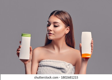 Portrait of attractive young woman with two shampoos on grey background. Making choice. Women care