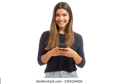 Portrait of attractive young woman using social media on mobile phone against white