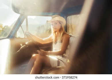 Portrait of an attractive young woman wearing a hat driving a car on sunny day