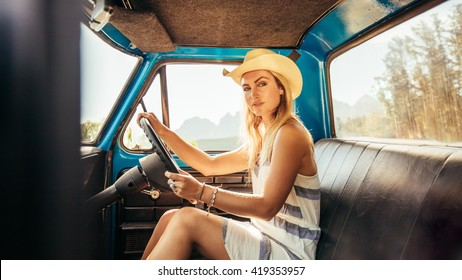 Portrait of an attractive young woman wearing a hat sitting on the driving seat of a car