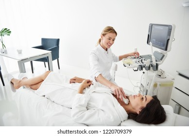 Portrait of attractive young woman in white bathrobe lying on daybed during medical examination while physician looking at her with smile