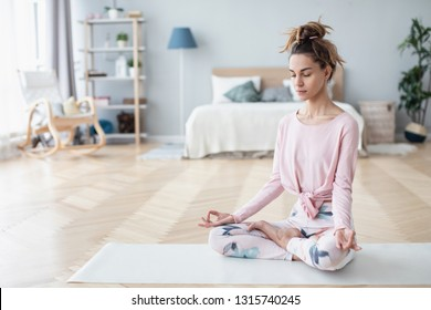 Portrait of attractive young woman working out at home, doing yoga exercise on white mat. Meditating and relaxing.