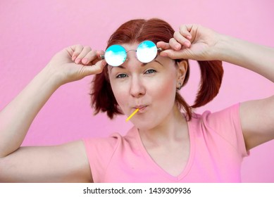 Portrait of audacious young woman in pink shirt with pigtails hairstyle, blue round sunglasses and lollipop candy standing agains bright pink wall raising sunglasses and smiling. Female power concept