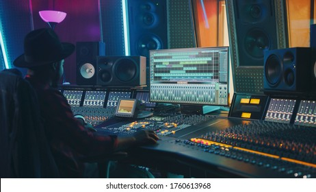 Portrait of Audio Engineer Working in Music Recording Studio, Uses Mixing Board Create Modern Sound. Successful Black Artist Musician Working at Control Desk.
