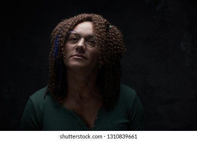 Portrait of an authentic adult woman with afro curls against a black wall in the studio. Unusual stylish woman with red hair