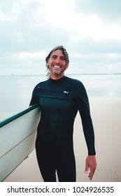 Portrait of authentic surfer in wetsuit with big surf board, smiling. Happy surf instructor, who enjoys his life.