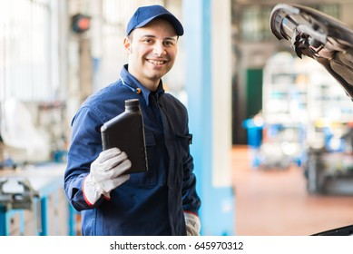 Portrait of an auto mechanic holding a jug of motor oil