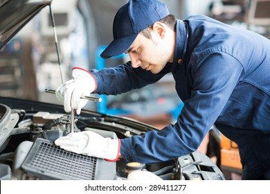 Portrait of an auto mechanic at work on a car in his garage