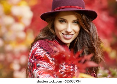 Portrait of an autumn woman over red and golden leaves