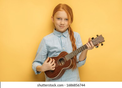 portrait of awesome caucasian child girl playing ukulele, attractive girl with natural red hair keen on music and instruments. isolated yellow background