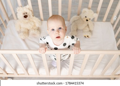 portrait of a baby 8 months old standing in a crib with toys in pajamas in a bright children's room after sleeping and looking at the camera, a place for text