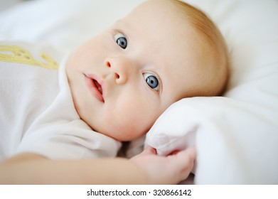 portrait of baby with blue eyes. A child resting on a bed