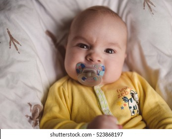 Portrait of baby boy angry, furious, frowning and agressive lying on blanket