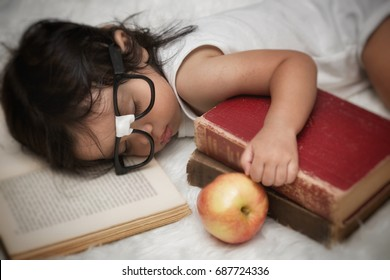 Portrait of a baby boy asleep while reading books.