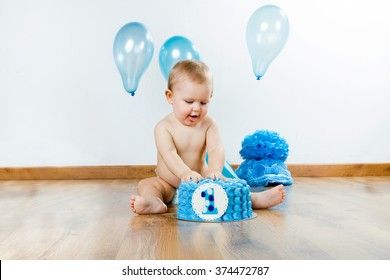 Portrait of baby boy celebrating her first birthday with gourmet cake and balloons.