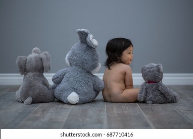 Portrait of a baby boy with his stuffed animal dolls.