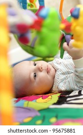 Portrait of baby boy on a playing mat at home