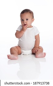 Portrait of a baby boy sitting with his hand on his chin with a quizzical expression on his face. Isolated on a white background.