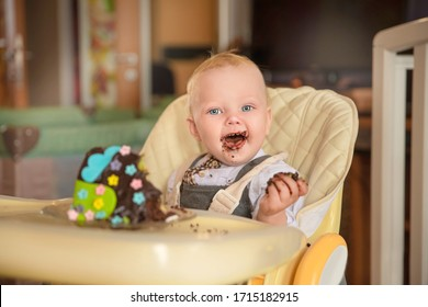 Portrait of a baby boy smeared with chocolate. With a piece of birthday cake.