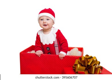 Portrait of baby boy standing in a huge Christmas gift box dressed as Santa Claus, isolated on white background