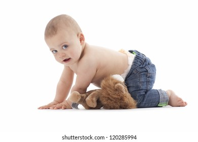 A portrait of a baby boy wearing blue jeans. High key image photographed in the studio.