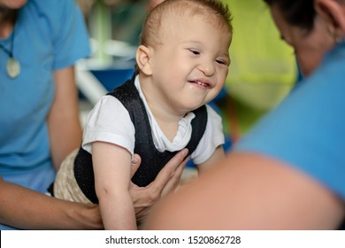 Portrait of a baby with cerebral palsy on physiotherapy in a children therapy center. Boy with disability has therapy by doing exercises. Little kid has musculoskeletal therapy in rehabitation centre.