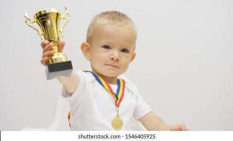 Portrait d'un bébé levant une tasse dorée, enfant offrant son trophée de victoire, attitude généreuse, conceptuel