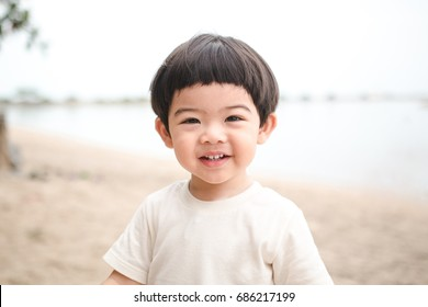 Portrait baby cute boy playing in the sandy beach, happy and Smiling child.