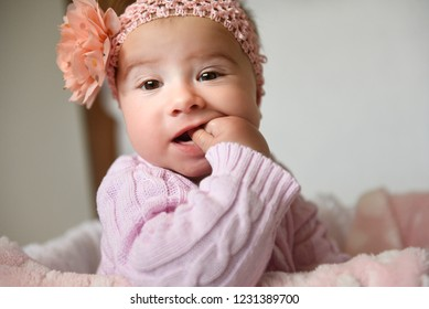 Portrait of baby girl with a bow on her head, posing in pink clothes, with a finger in her mouth