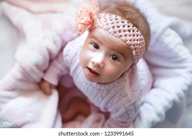 Portrait of baby girl with a bow on her head, posing in pink clothes