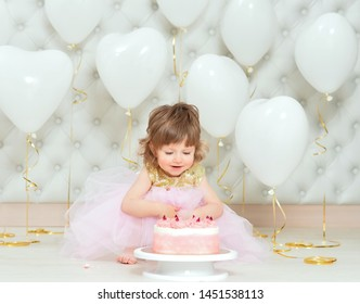 Portrait of baby girl with cake on her birthday