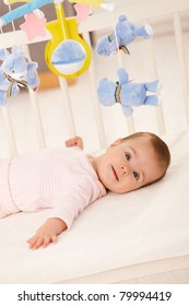 Portrait of baby girl in infant bed with toy bear.?