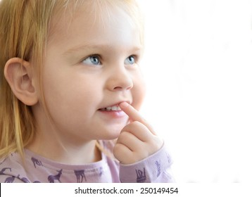 Portrait of a baby girl pointing finger to her mouth isolated on white