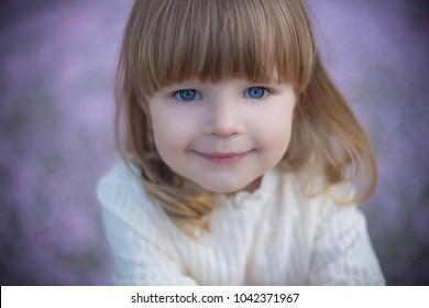 portrait of baby girl in vintage dress smiling on lavander petal spring backgroud