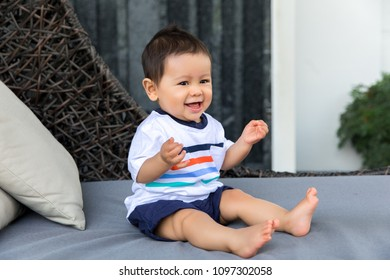 Portrait baby happiness lively sitting on bed in holiday, mixed race Romanian Thai 1 year old.