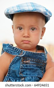 Portrait of baby in jeans suit and blue cap