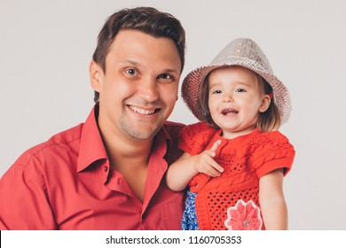 Portrait: baby on the hands of father. Fashion for family. isolated photo of people in red. people in hats