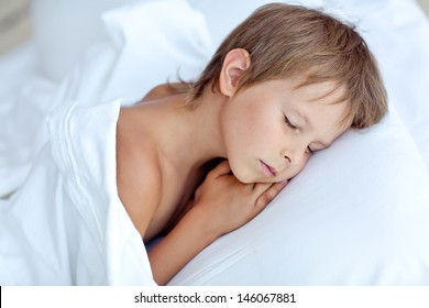 Portrait of a baby sleeping on a white pillow and blanket