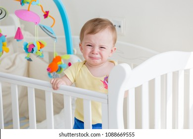 Portrait of baby standing in cot and crying