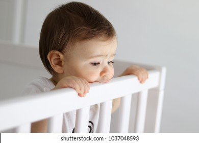Portrait of baby staying in his baby cot looking sadly outside with frowned brows