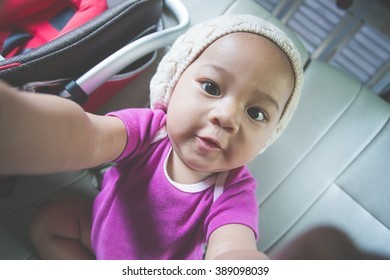 portrait of a baby taking selfie of her self using phone camera