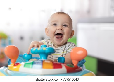 Portrait of baby toddler in baby walker. Expressive child plays toys.