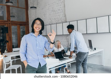 Portrait from back of african guy in checkered shirt standing beside table with laptops on it and asian man on foreground. Team of talented young specialists working on joint project and having fun.