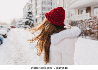 Portrait from back of amazing girl posing with long hair waving in cold winter day. Outdoor photo of dreamy woman in woolen red hat looking in distance standing at snowy street.
