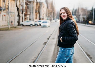 Portrait from back of elegant girl with long hair walking on on city background. She has black leather jacket and jeans. She is smiling to camera.
