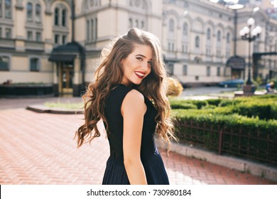 Portrait from back of elegant girl with long curly hair walking on steer on old building background. She has black dress and red lips. She is smiling to camera.